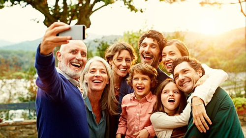 A photo of a family smiling and taking a group selfie.