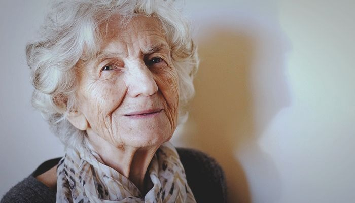 older woman wearing a light scarf smiling