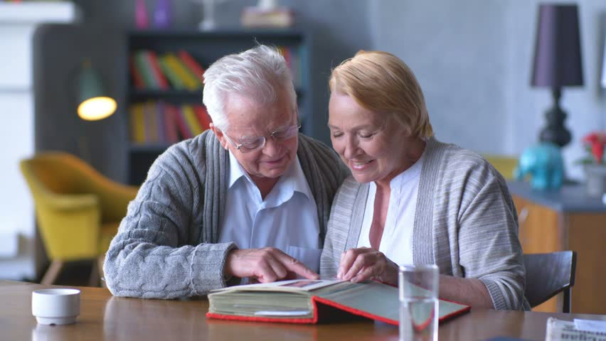 Elderly father and adult daughter looking at family photo album