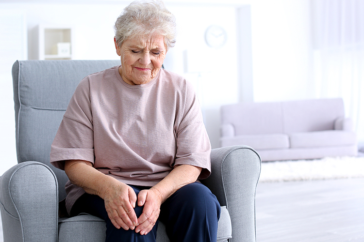 elderly lady seated holding her knee because she is in pain