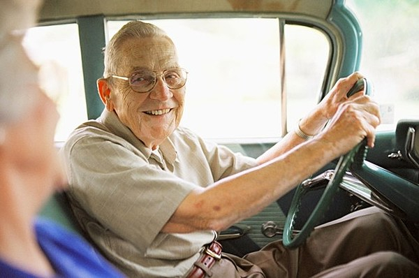 Elderly man wearing glasses smiling, sitting in a car with his hands on the steering wheel.