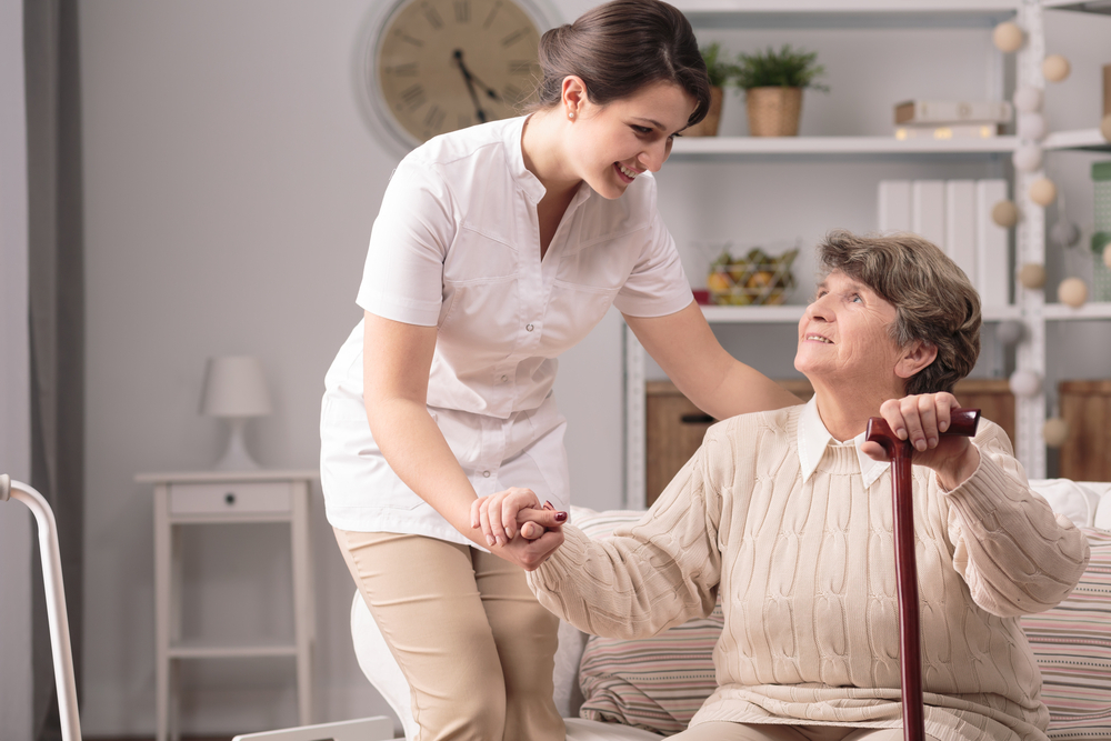 caregiver helping elderly lady from the couch
