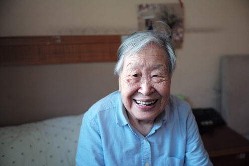 An elderly lady wearing blue and smiling