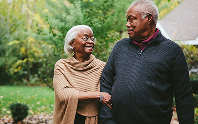 Black old married couple walking arm and arm.