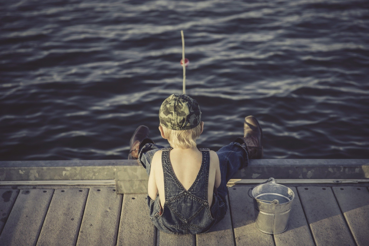 little white blond boy wearing a hat sitting down and fishing off the dock