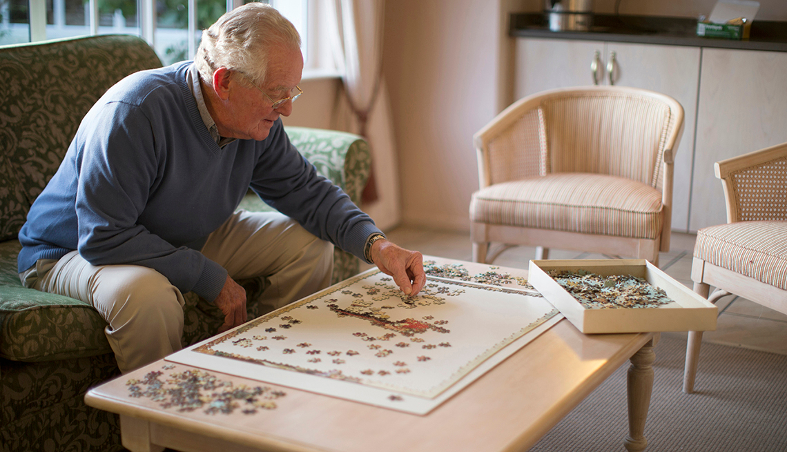 old man wearing glasses looking focused as he works on his puzzle