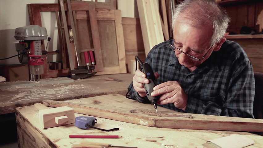 Old man wearing glasses and wearing a plaid shirt wood working with hand tool